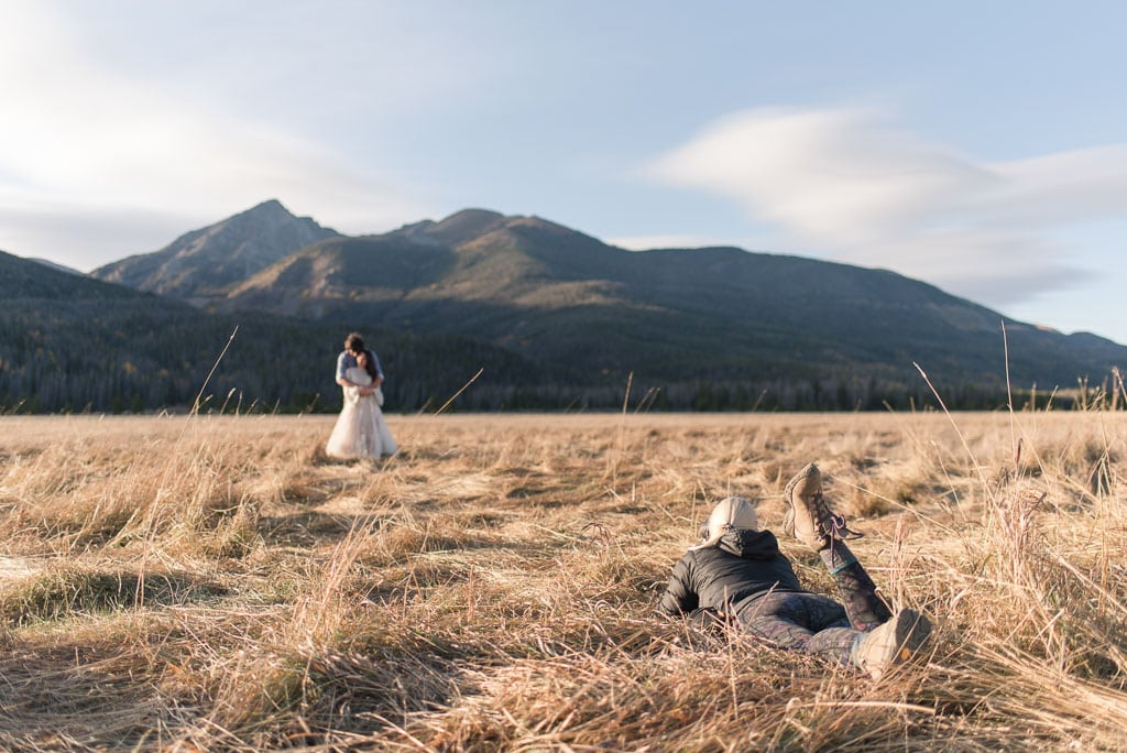 Photographer in a field taking pictures of happy couple with mountains in the background