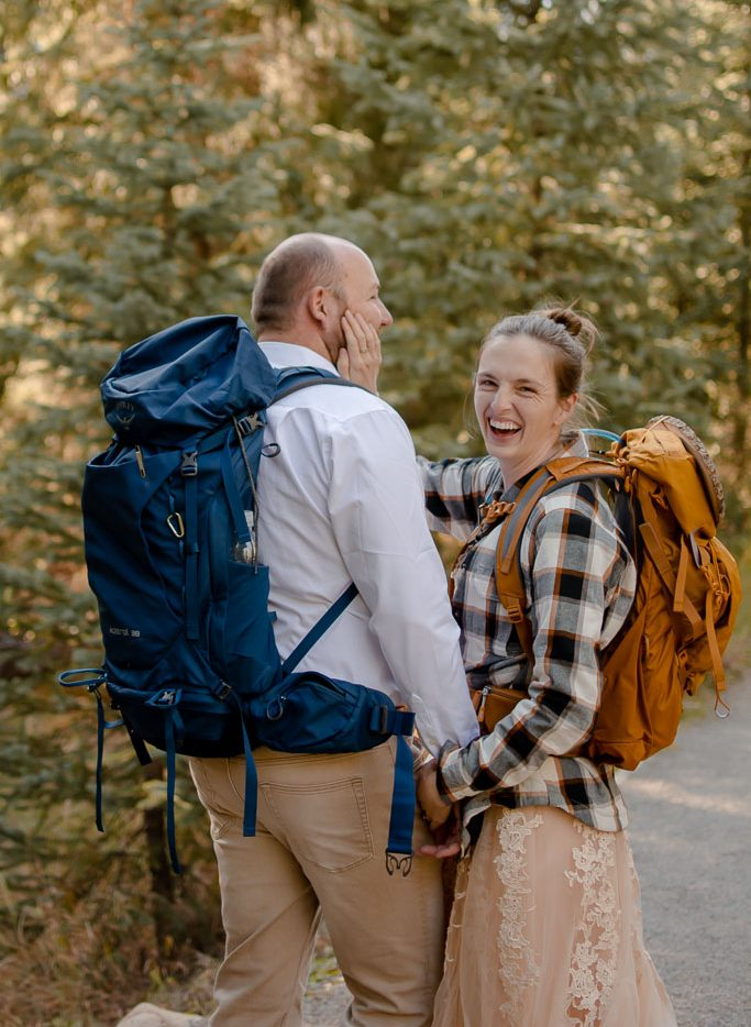 Adventurous couple laughing and hiking through the woods together for elopement