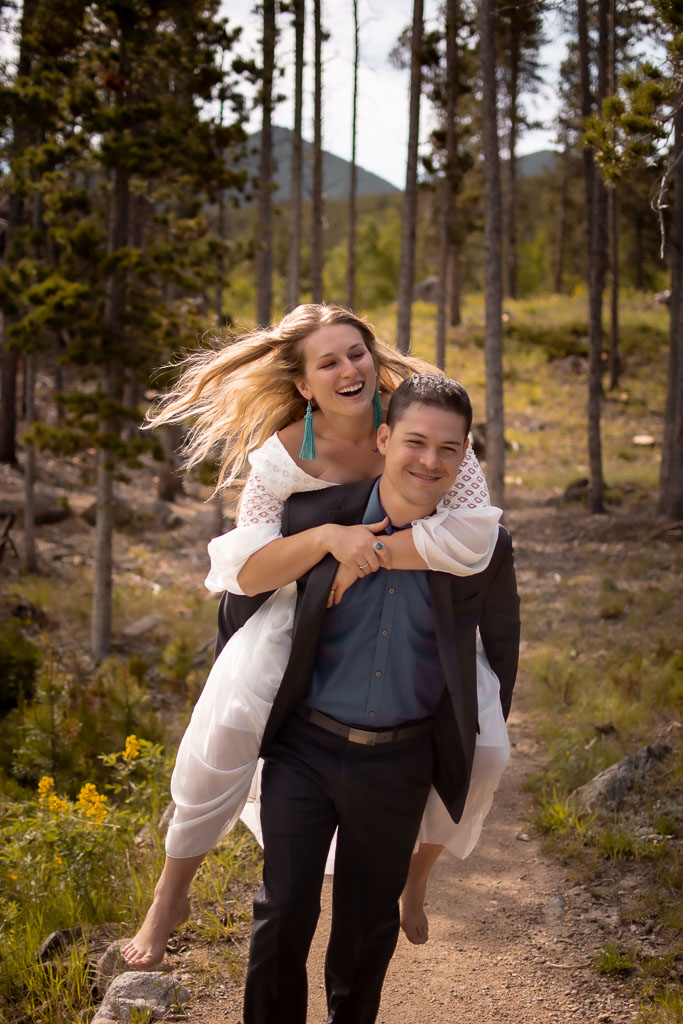 Groom giving a piggy back ride to bride in a forest in Rocky Mountain National Park in Colorado
