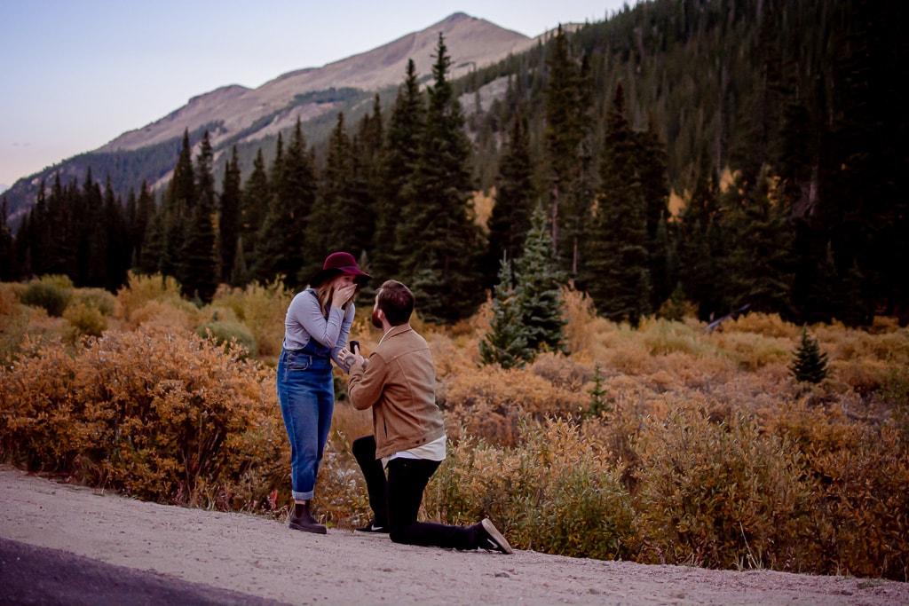 Man proposing to woman down on one knee in Colorado with mountain backdrop in the fall