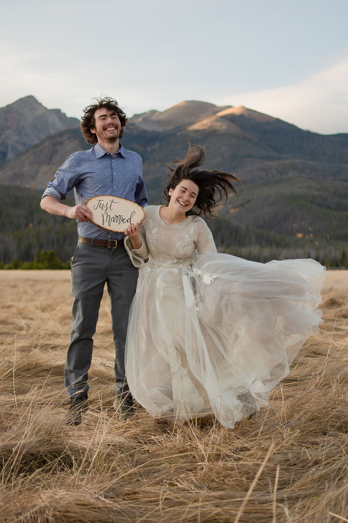 Excited couple with Just Married sign jumping up and down at Rocky Mountain National Park in Colorado