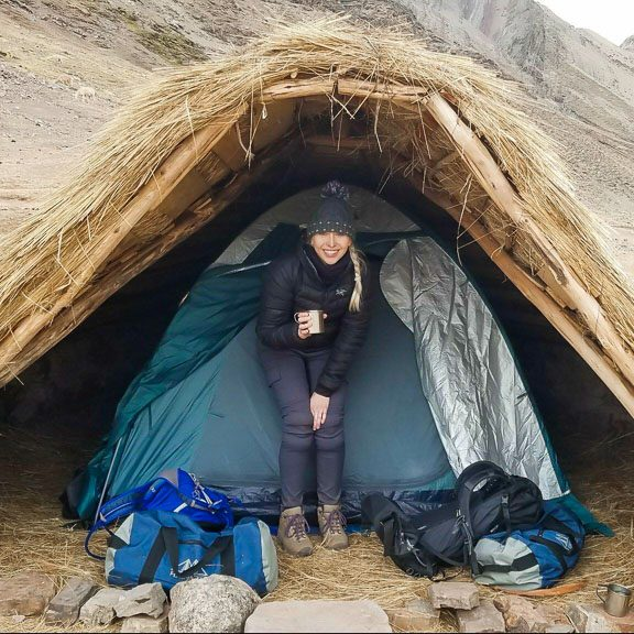 Photographer traveling and camping with a tent and mug of hot beverage