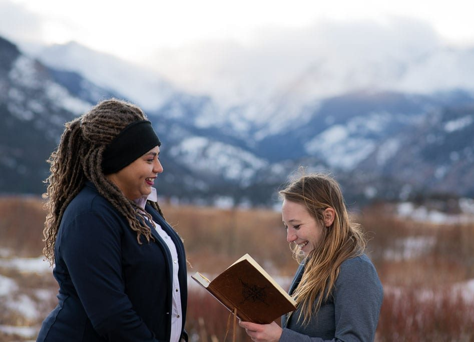 LGBT couple smiling and saying their vows on wedding day in snowy Rocky Mountain National Park in Colorado