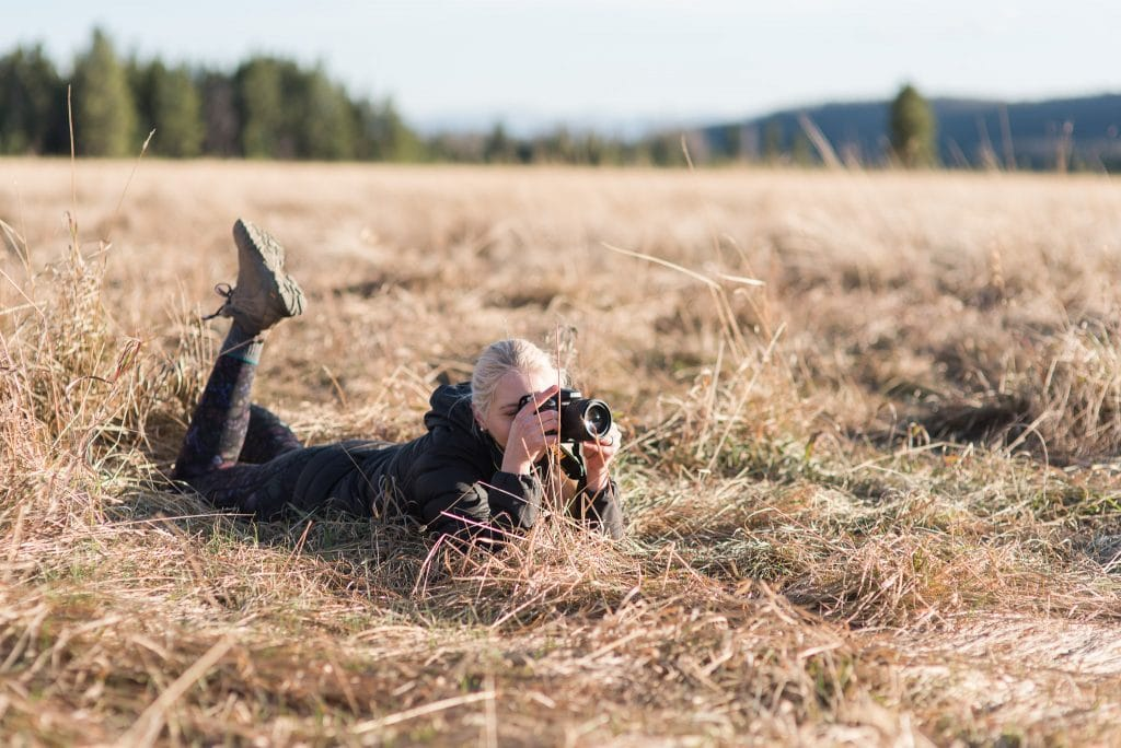 Adventure photographer lying in the grass field taking photographs