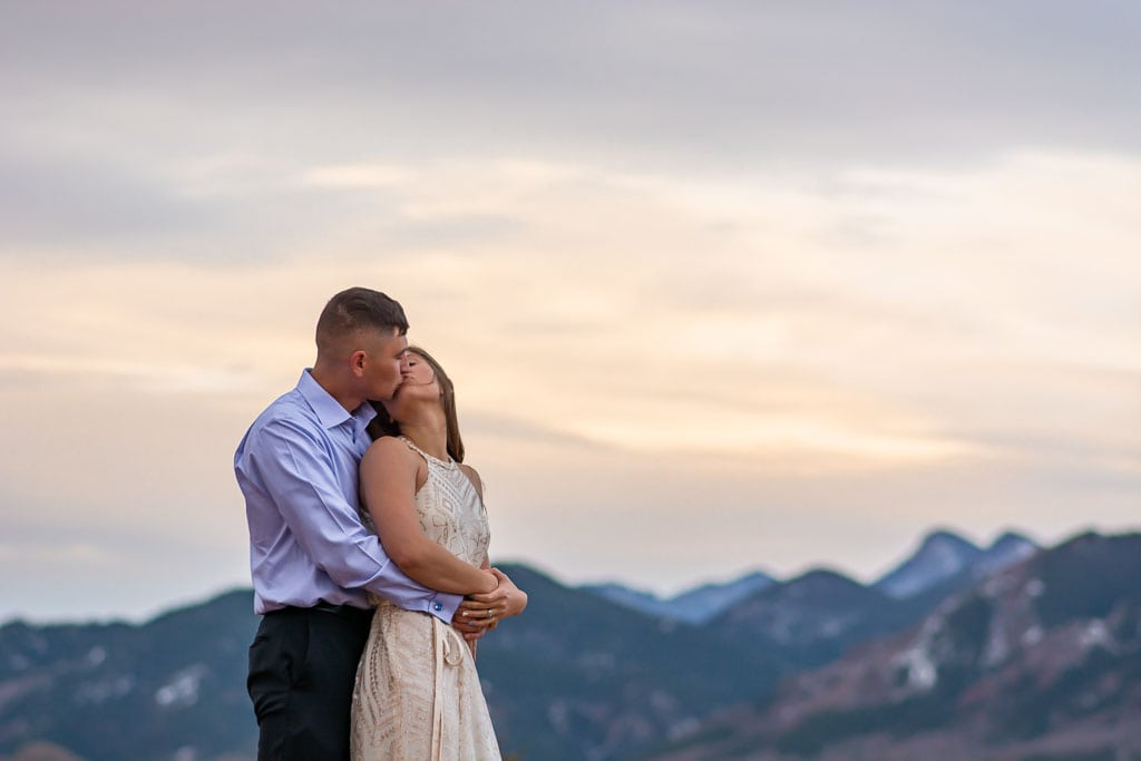 Bride and groom holding each other and kissing with mountains in the background at sunrise in Colorado