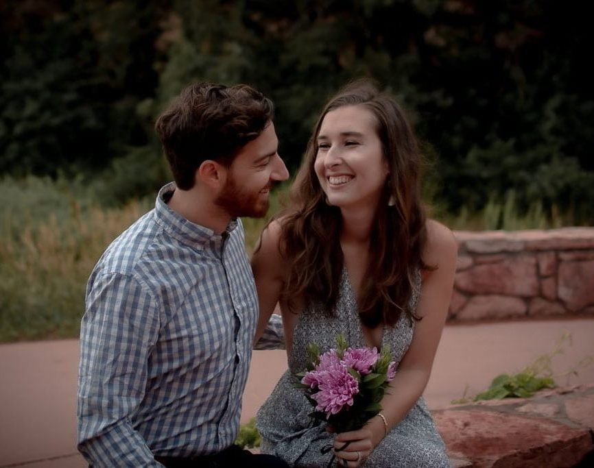 Couple sitting next to each other and laughing together in Garden of the Gods in Colorado