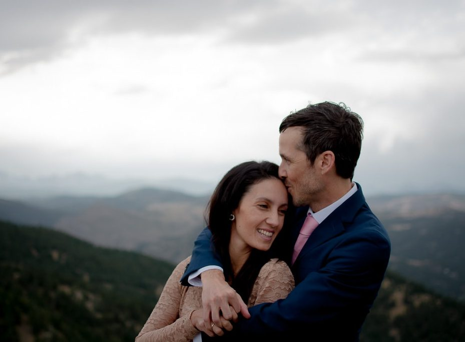Bride and groom embracing each other and smiling with mountain views in the background in Colorado