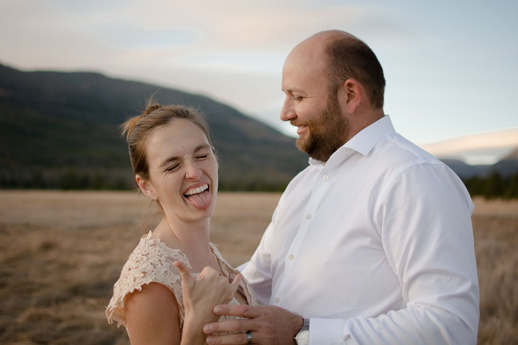 Bride making a happy face with tongue out and rocker hand gesture while groom laughs