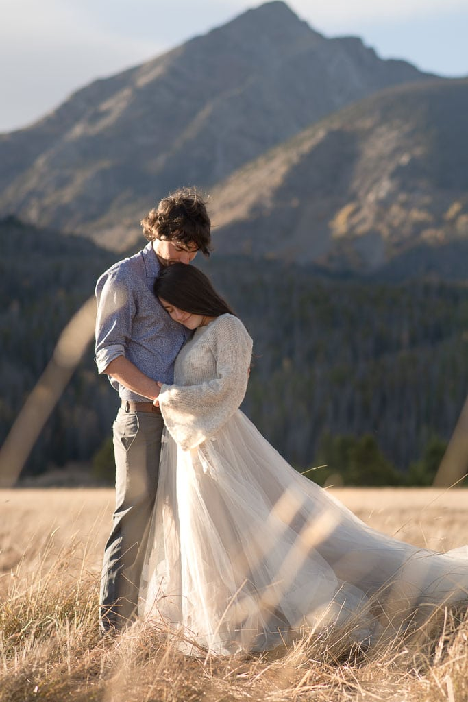 Bride and groom embracing each other on their wedding day in a field with a mountain in the background