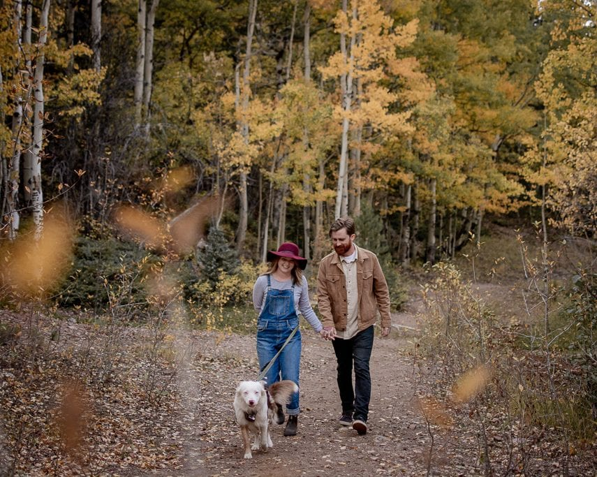 Casually dressed couple walking together in a forest with fall leaves and their cute dog