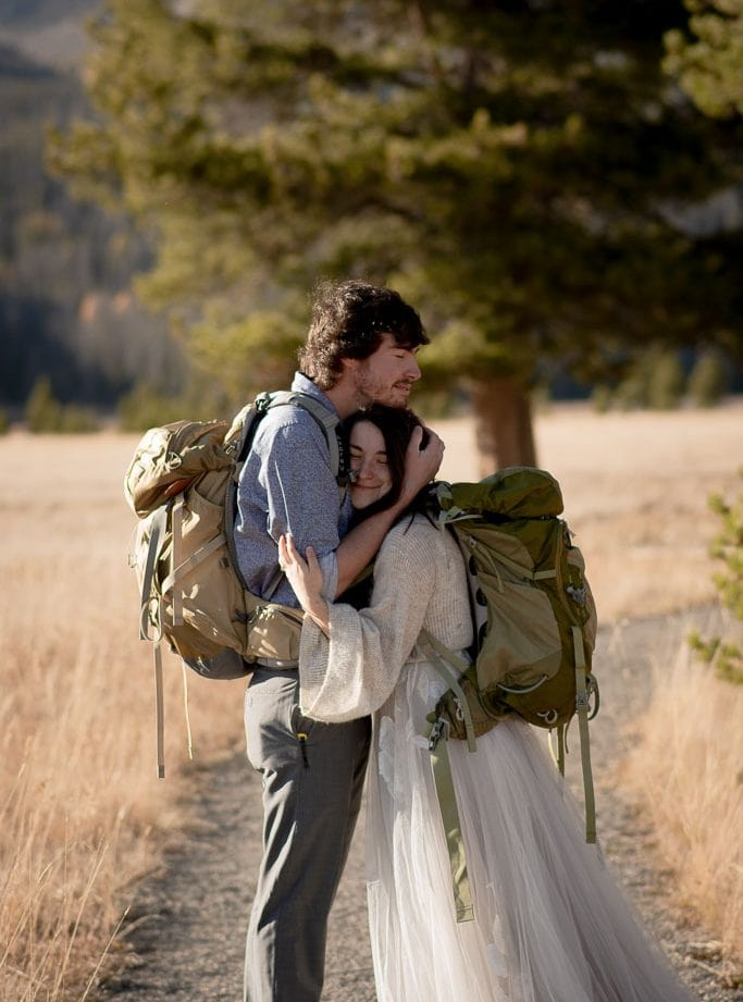 Hiking bride and groom with daypacks on a trail hugging each other