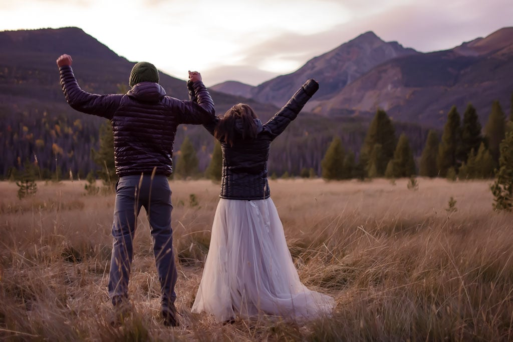 Couple holding hands and jumping for joy on their wedding day in Rocky Mountain National Park in Colorado