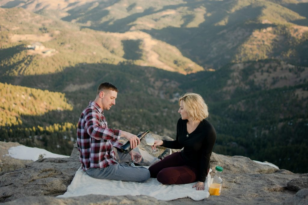 Couple sharing a romantic picnic with mimosas on a white blanket with mountains in the background