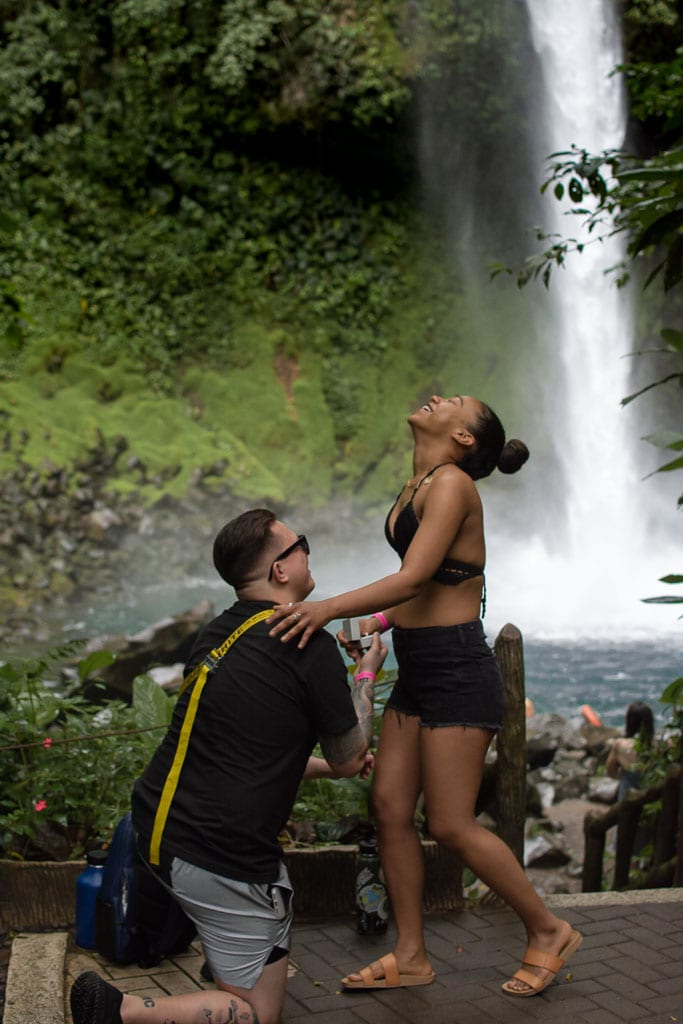 Man proposing to happy smiling woman in front of a waterfall in Costa Rica