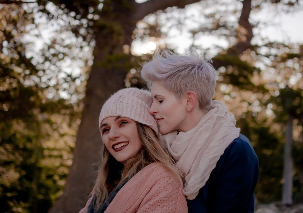 Happy same-sex couple embraces each other on a cold winter day while on a hike in the forest
