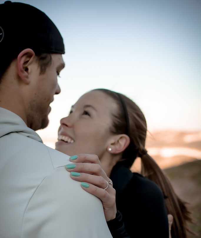 Happy athletic couple running together in the mountains and embracing after just getting engaged
