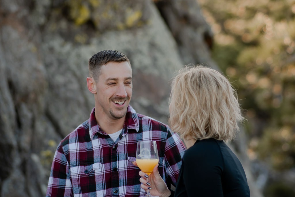 Laughing couple drinking mimosas together in the mountains in Colorado