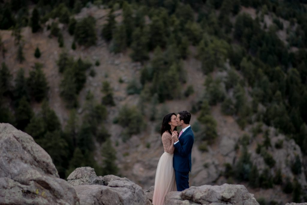 Happy eloping couple holding hands and kissing standing on rocks with mountains in the background