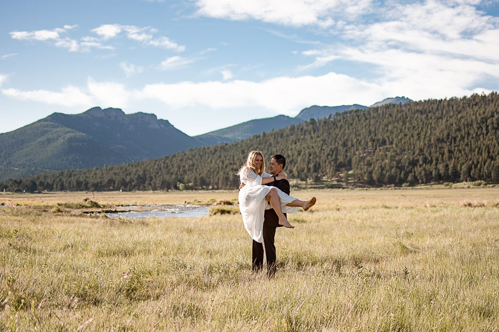 Groom carrying his bride in a field in Colorado while she is laughing