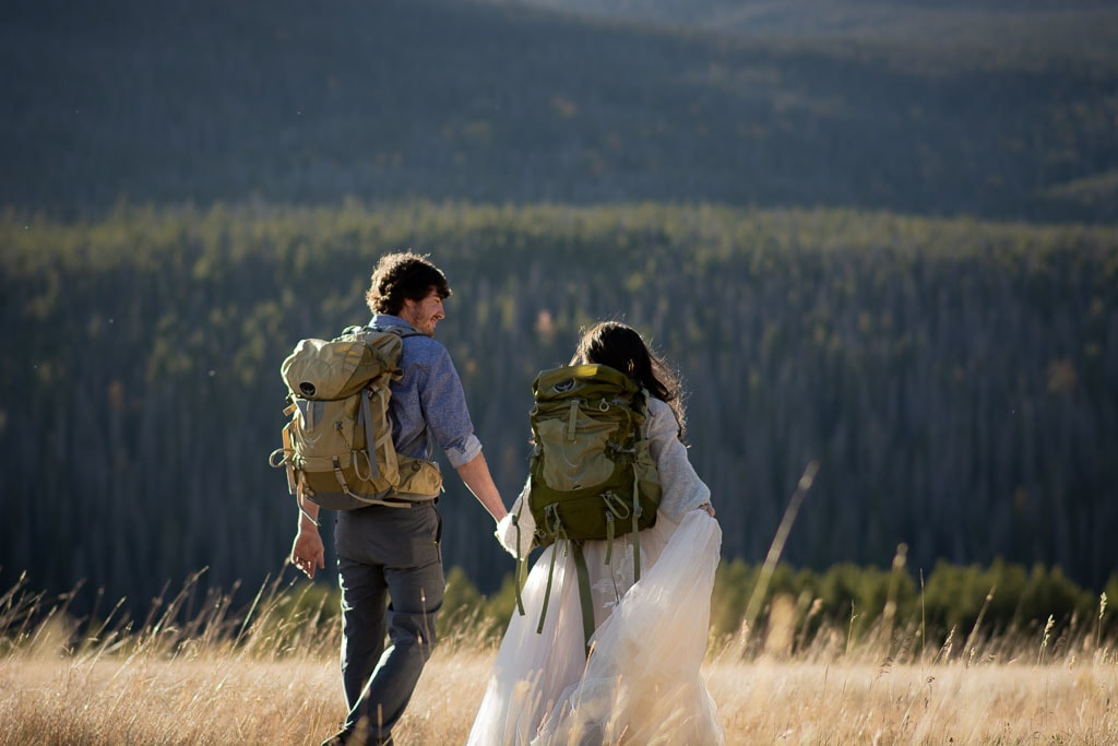 Bride and groom wearing their backpacks are walking through a field together holding hands