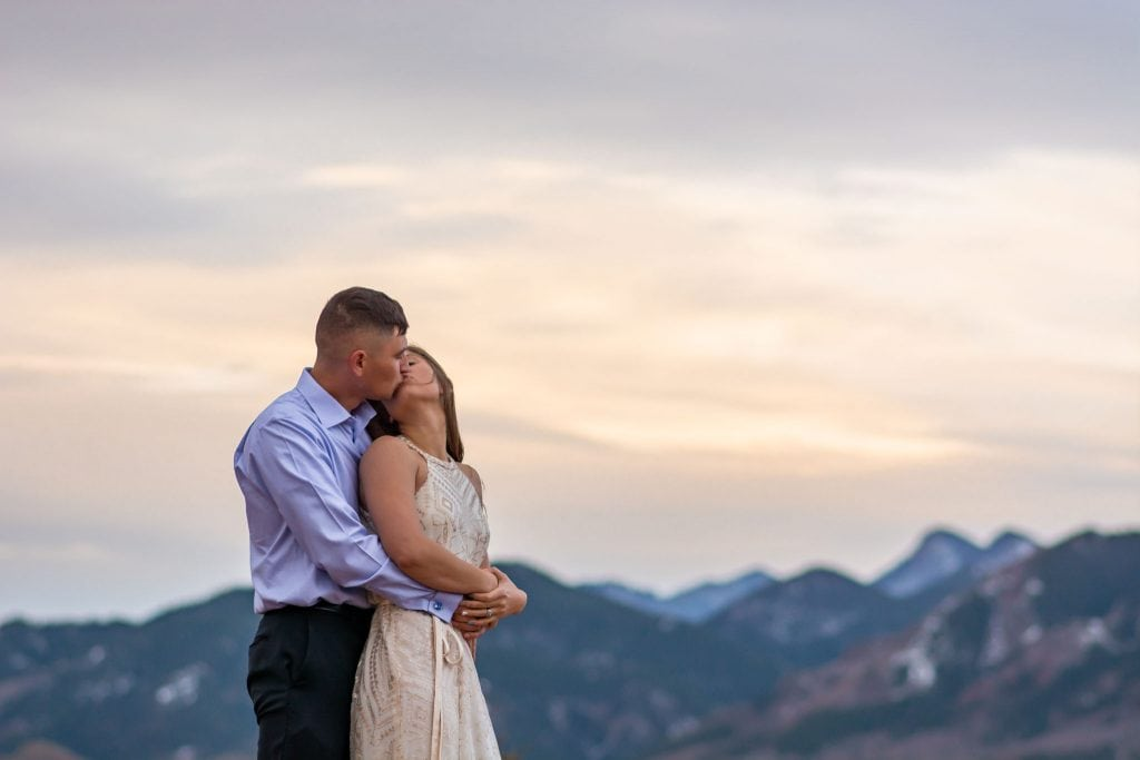 Couple eloping at sunrise kisses with Pikes Peak in the distance