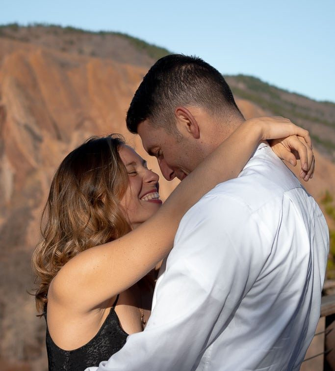 Smiling woman in a black dress hugging her man in Roxborough State Park in Colorado
