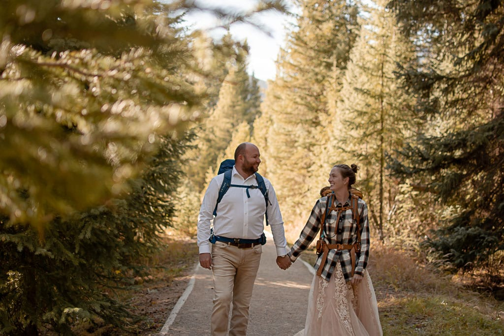 Couple on a trail in the forest in their wedding attire wearing backpacks and holding hands