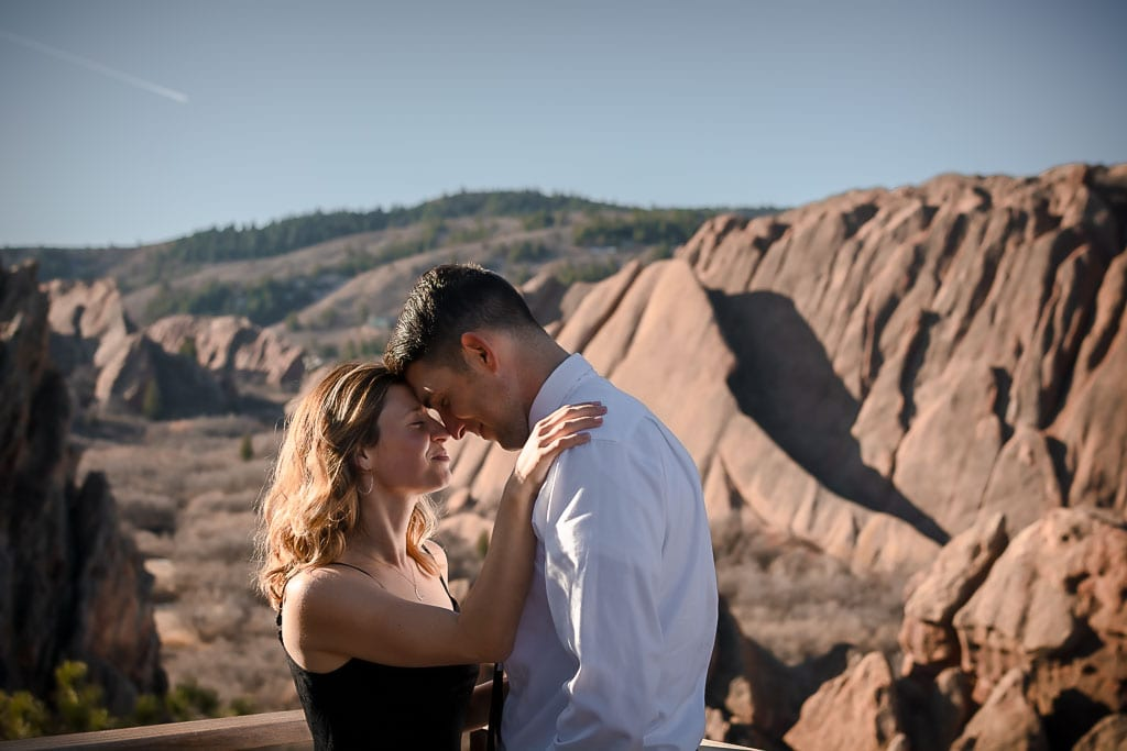 Eloping couple touching foreheads and smiling together in Roxborough State Park in Colorado