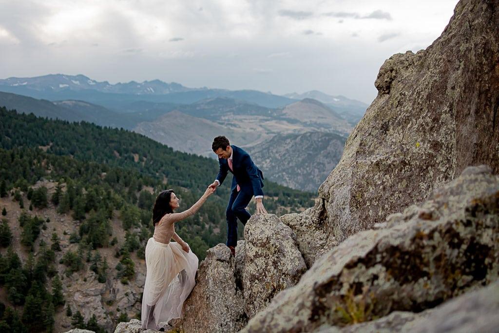 Groom helping his bride climb up rocks in Boulder Colorado