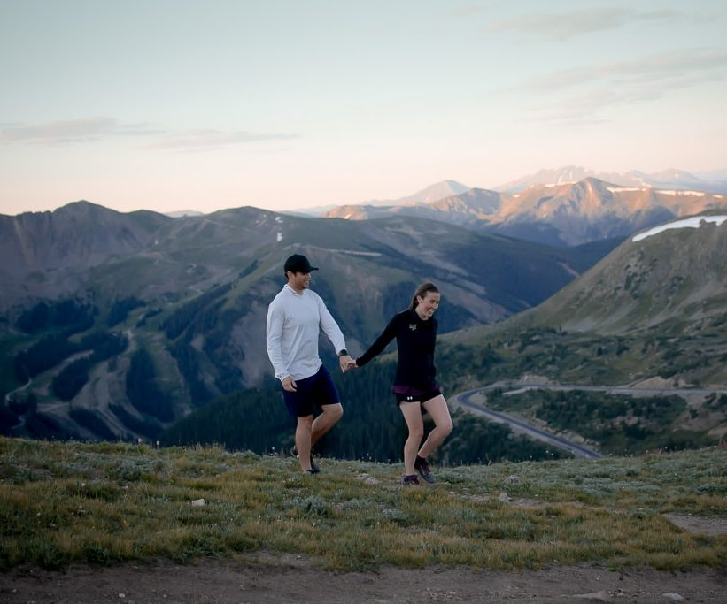 Trail running couple holding hands and walking through a grassy field in the mountains of Colorado