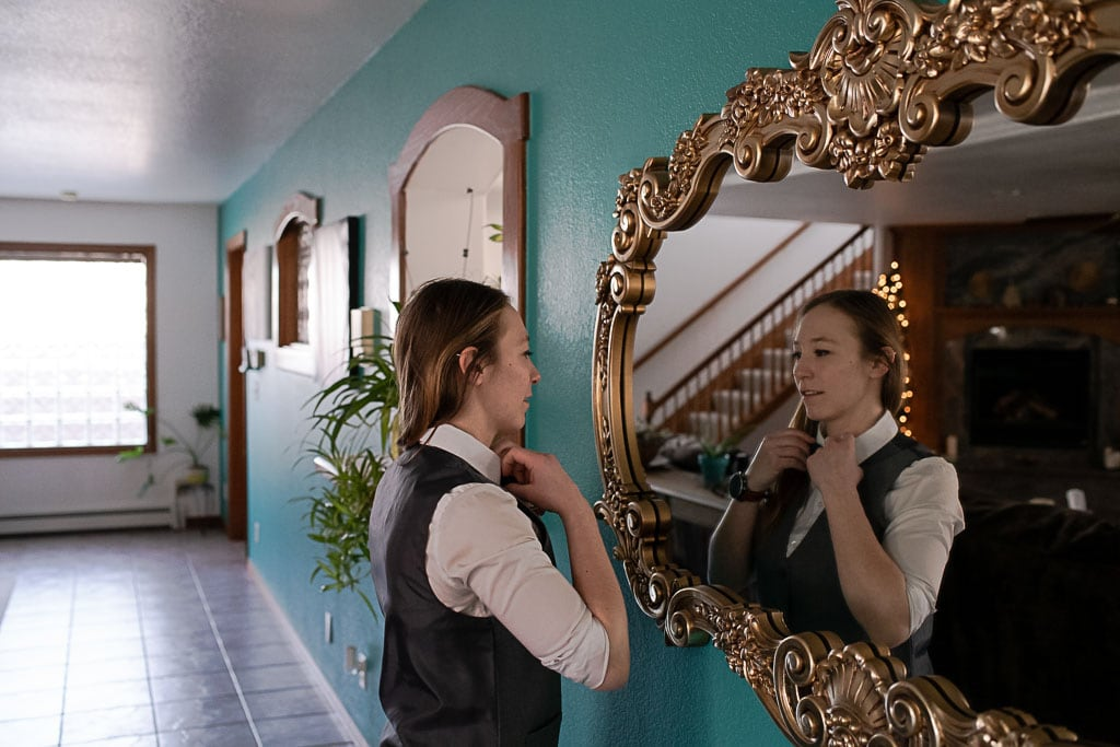 Woman looking in the mirror and fixing her bow tie on her wedding day