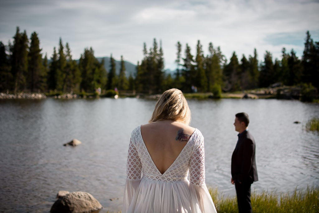 A bride walks toward her groom at Sprague Lake in Rocky Mountain National Park on a sunny day