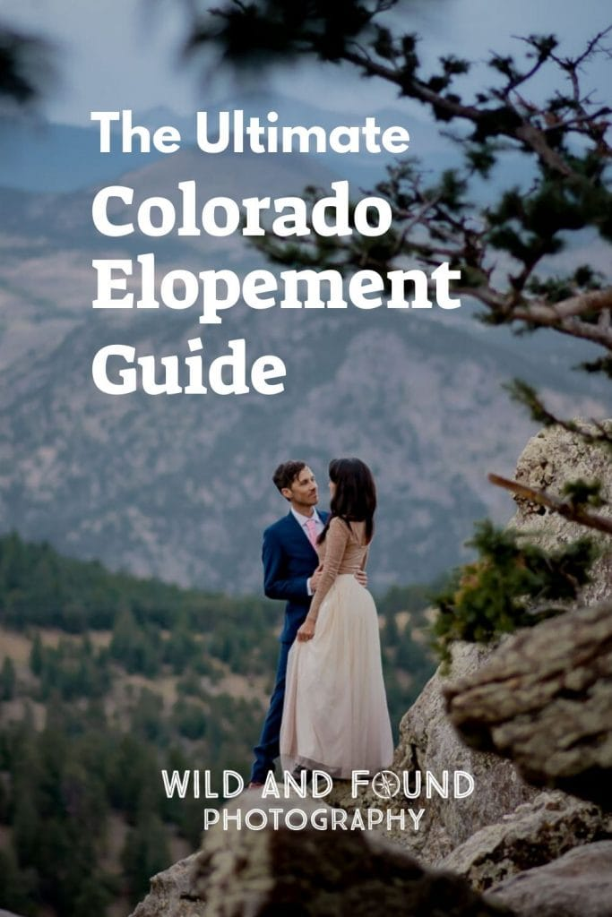 Bride and groom standing on a rock in front of Colorado Mountains