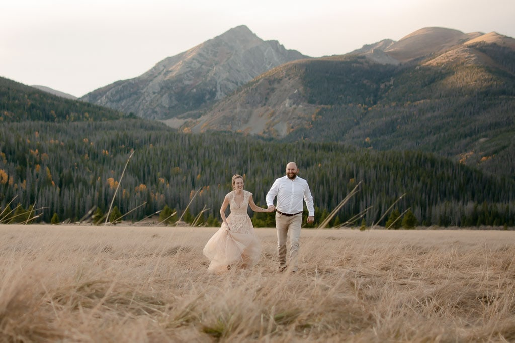 Eloping couple running in a field in front of mountains at sunset in Colorado