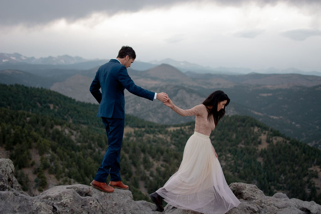 Bride and groom holding hands while walking through the mountains in Colorado