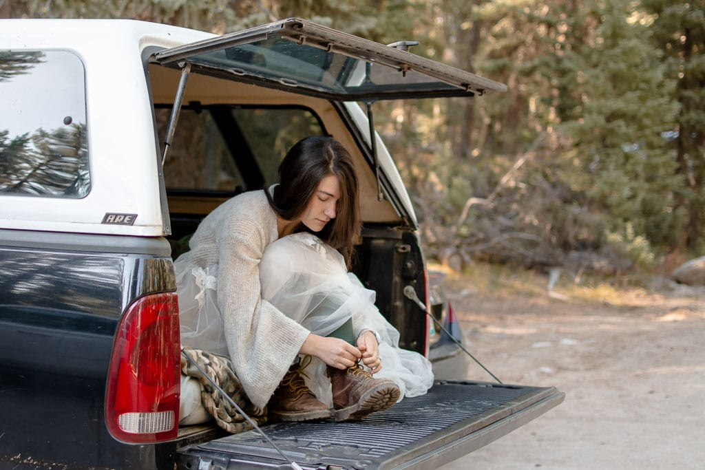 Bride sitting in the back of a truck putting on hiking boots for her elopement
