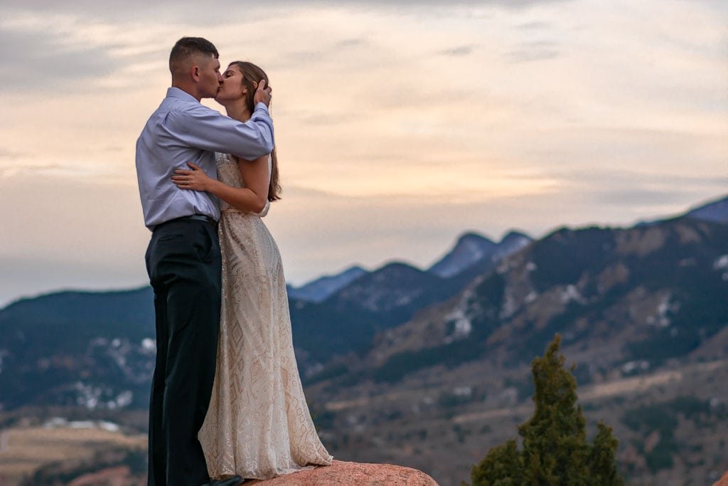 Couple's sunrise elopement at Garden of the Gods with Pikes Peak in the distance