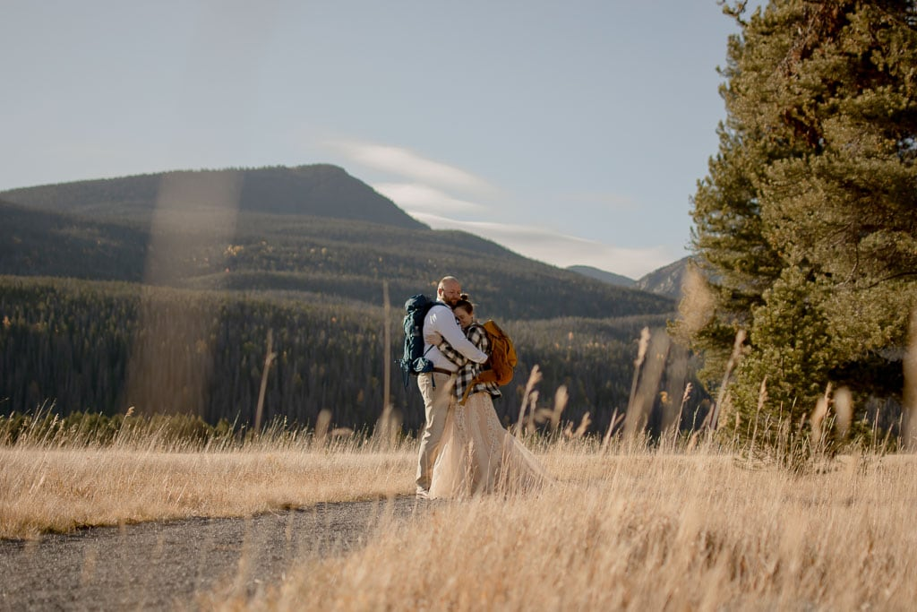 Couple hiking on a gravel trail among tall grass for their elopement in Rocky Mountain National Park