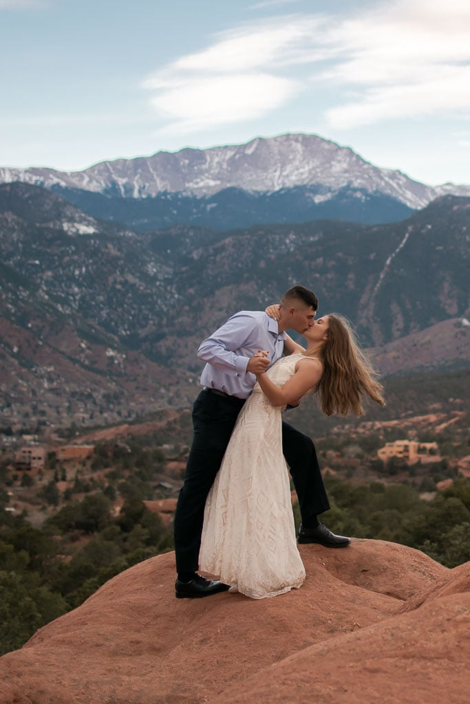 Self-solemnizing couple kisses on a red rock with Pikes Peak in the distance