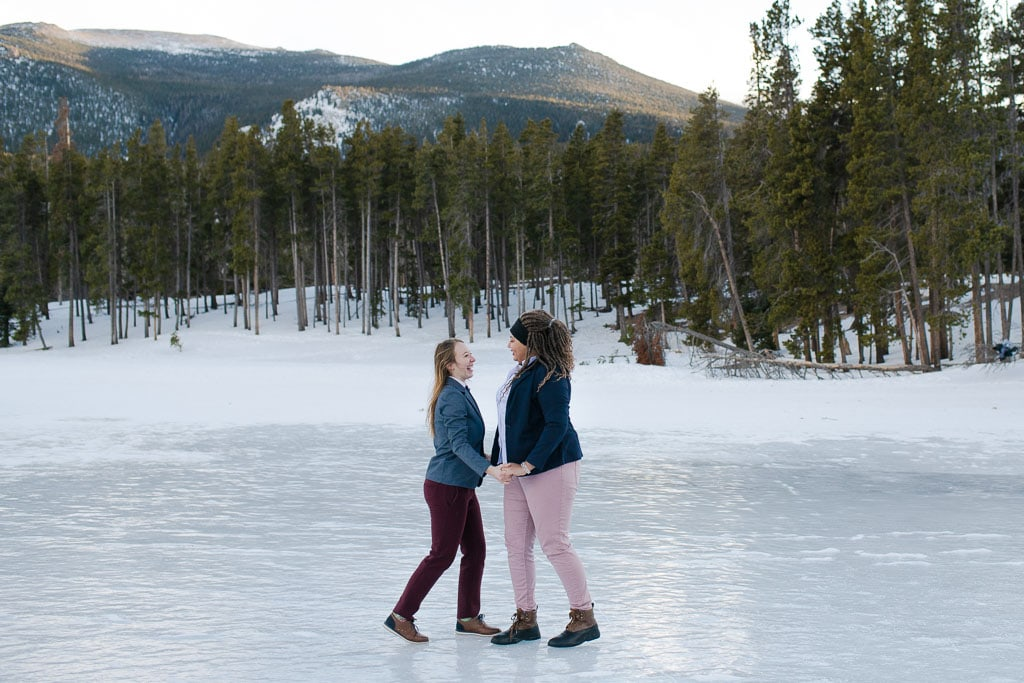 Lesbian couple standing on a frozen lake with mountains and pine trees in the distance