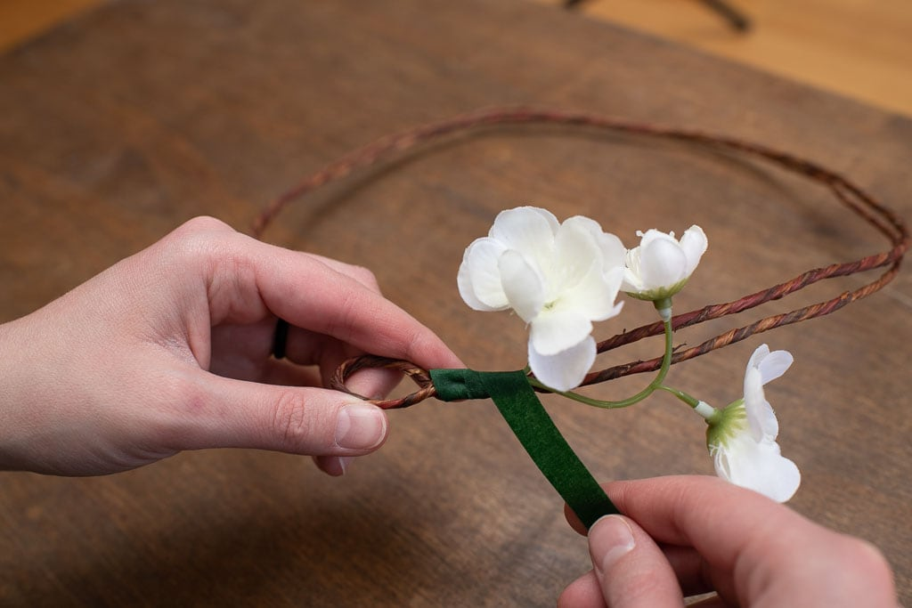 Hands attaching a white flower to craft wire using green floral tape