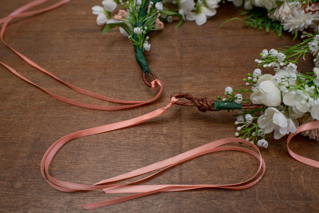 Close up view of pink ribbons tied to a flower crown