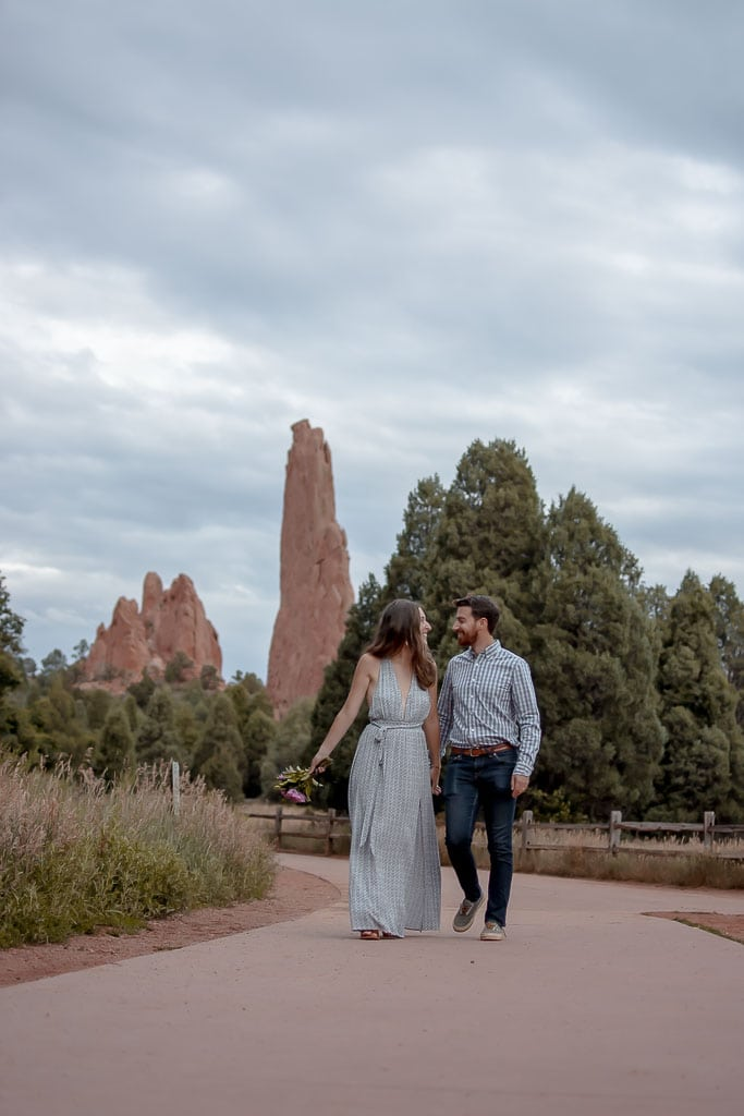Eloping couple holding hands and walking in Three Graces Plaza in Garden of the Gods