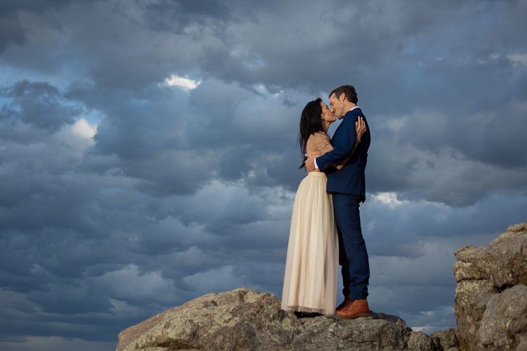 Eloping couple stands on the top of some rocks with a moody and cloudy sky behind them