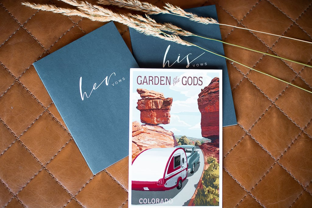 Garden of the Gods post card and blue vow books for an elopement