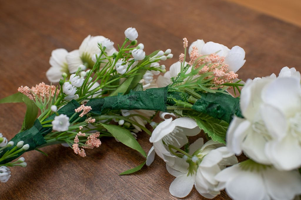Close up detail of flower crown with pink and white flowers secured using green floral tape