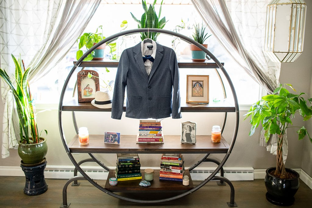 Grey suit jacket and bow tie hanging from circular decorative shelving unit with plants on either side