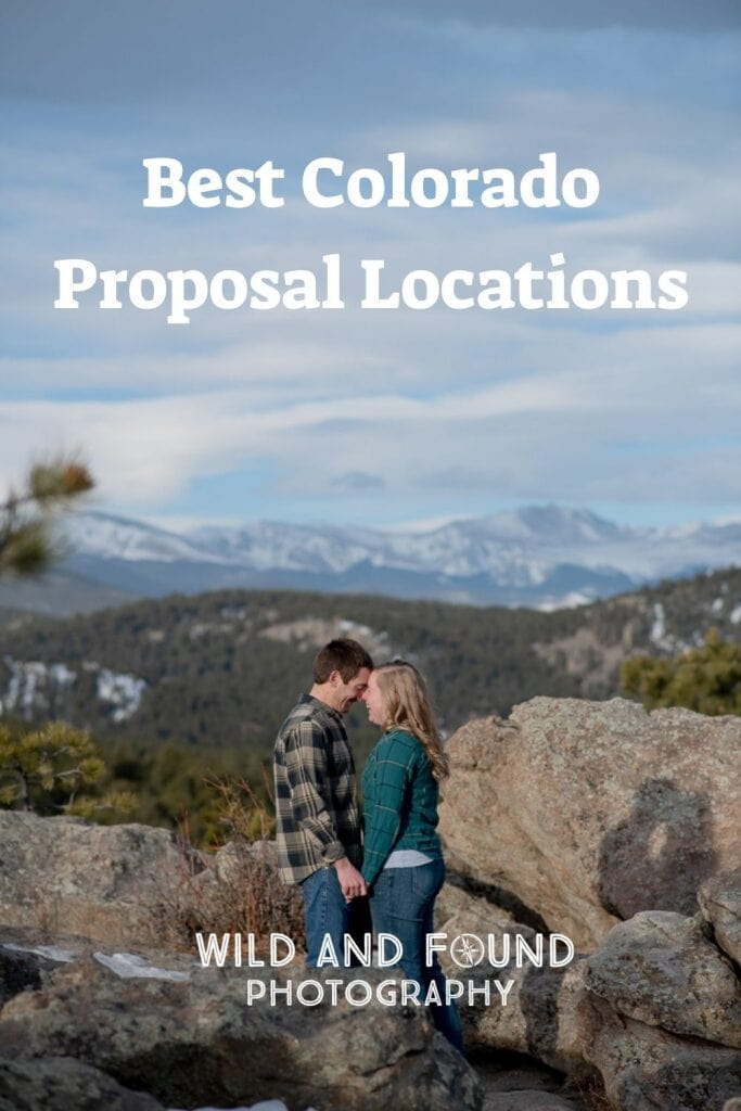 Engaged couple standing on rocks laughing with Colorado mountain views in the background