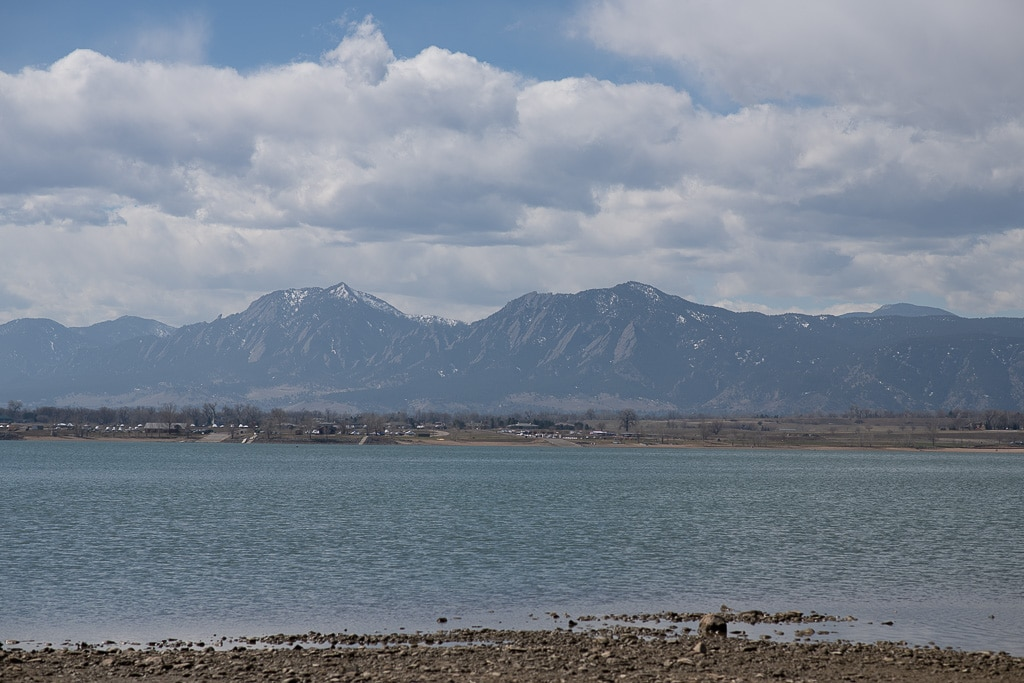 Boulder reservoir shoreline with Flatirons in the background on a partly cloudy day