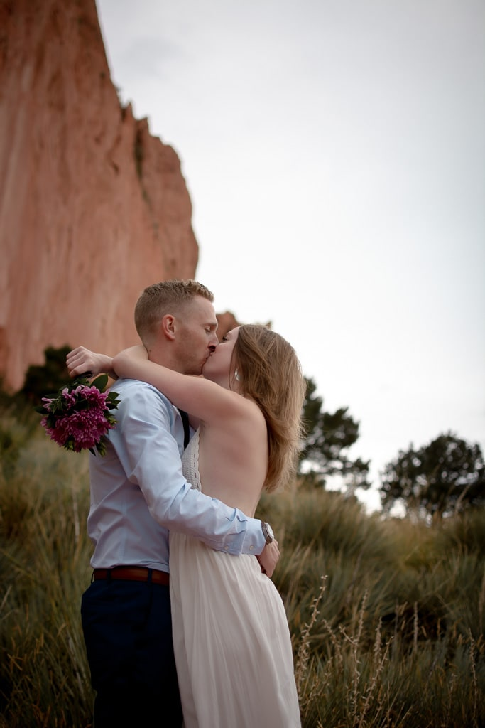Bride and groom kissing at Garden of the Gods in front of green grass and red rocks